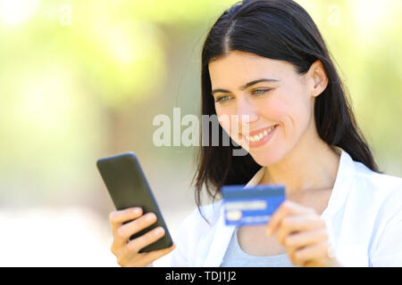 Happy adult woman paying on line with credit card and smart phone in a park - Stock Image