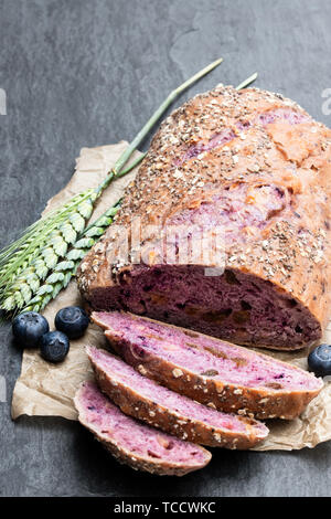 Blueberry  and chia seed bloomer on black stone table - Stock Image
