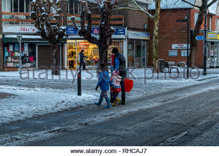Fleet, Hampshire, UK. 2nd Feb, 2019. Heavy overnight snow followed by a sharp frost made for a difficult early morning for pedestrians and motorists. Image: A family make their way to the local park for an early morning toboggan ride. Credit: Images by Russell/Alamy Live News - Stock Image