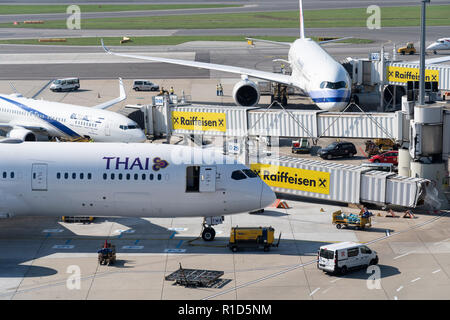 A Thai Airways passenger jet docked to a passenger bridge at Vienna Airport - Stock Image