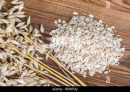 Rolled oats and common oat spikes on brown wood. Avena sativa. Oat flakes pile close-up. Decorative dry ears, cereal grains, vintage wooden backgroud. - Stock Image