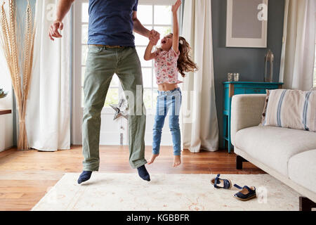 Girl and dad jumping up holding hands, her arm in the air - Stock Image