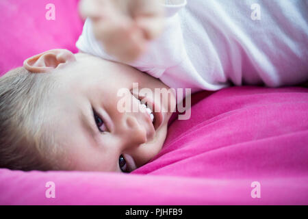 Portrait of a baby lying on the eyes laughing. - Stock Image