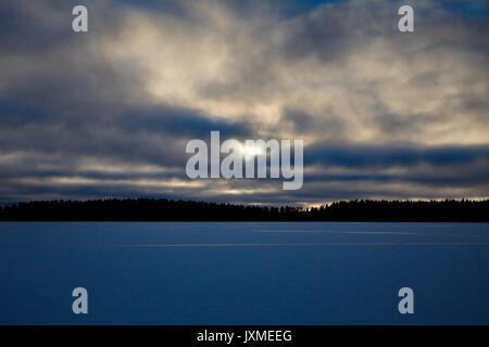 Clouds are towering over a frozen lake at dusk. - Stock Image