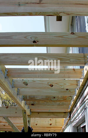 Construction of the underside a house's new exterior wood deck in progress - Stock Image