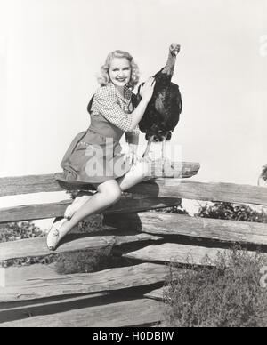 Woman sitting on fence petting her turkey - Stock Image