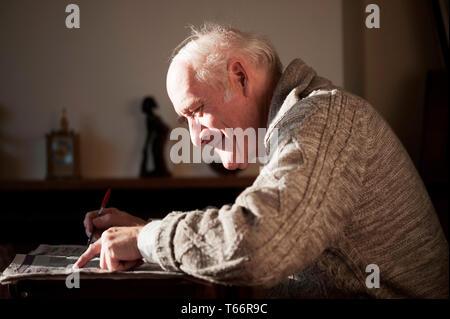 Senior man reading newspaper - Stock Image