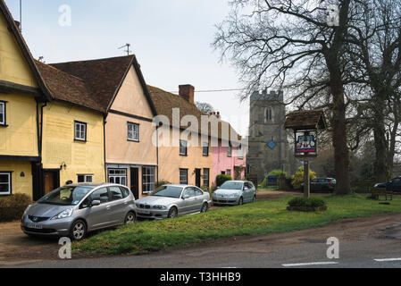 View of cottages and Church Of St John The Baptist beside the small village green in Stoke by Clare, Suffolk, England, UK - Stock Image