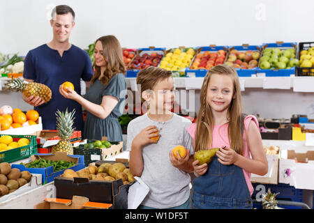 Two lucky kids looking for fresh delicious fruits  in local supermarket with family - Stock Image