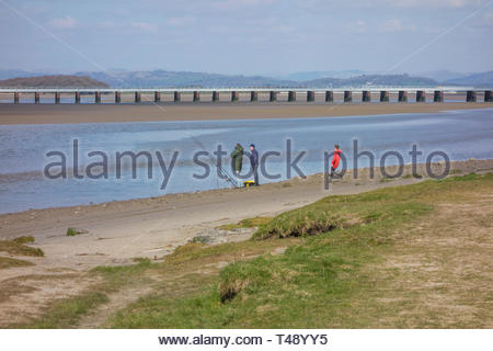 Fishermen on the shore looking out over the Kent Estuary by the attractive seaside village of Arnside, Cumbria, England - Stock Image