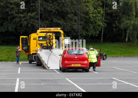 Lone young female motorist having broken down car recovered by the AA. - Stock Image