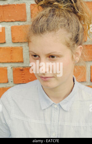Young independent woman in front of a brick wall - Stock Image