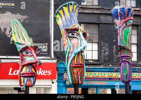 Colourfully decorated sculptured heads in a street in Dublin, Ireland, Europe. - Stock Image