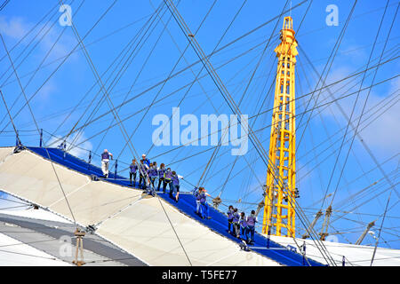 Up At The O2  millennium arena dome roof & rooftop  Skywalk walk group of people wear blue overalls climbing to top of o2 arena tour guide leader UK - Stock Image