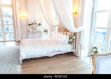 Beautiful luxury classic white bright clean interior bedroom in baroque style with king-size bed, large window, armchair and flower composition - Stock Image