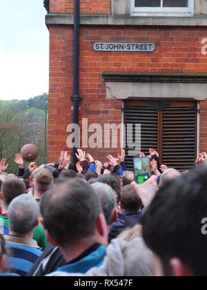Ashbourne Shrovetide Football 2019. Hands in a sea of players grasp for the ball on St John Street as play enters town during the Ash Wednesday game. - Stock Image