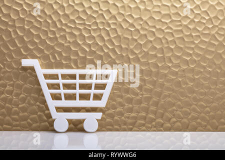 White Shopping Cart Leaning Against Textured Golden Backdrop - Stock Image