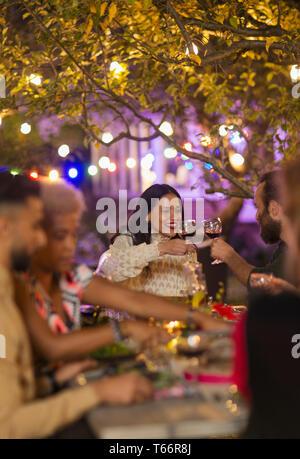 Friends toasting wine glasses, enjoying dinner garden party - Stock Image