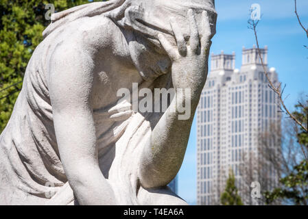 The Weeping Woman statue at the Gray lot in Historic Oakland Cemetery with downtown Atlanta, Georgia's 191 Peachtree Tower in the background. (USA) - Stock Image