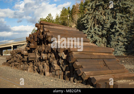 A stack of creosote railroad ties on the side of the tracks in the switching yard behind the General Feed & Grain mill, in Bonners Ferry, Idaho, USA - Stock Image