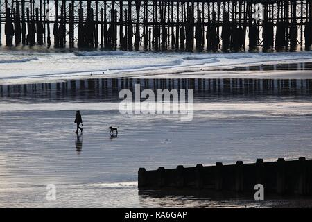 Hastings, East Sussex, UK. 02 Jan, 2019. UK Weather: As the sun sets in Hastings, East Sussex a few people take a leisurely walk along the seashore front as the tide is out. © Paul Lawrenson 2018, Photo Credit: Paul Lawrenson / Alamy Live News - Stock Image