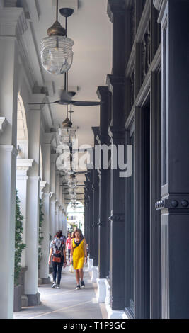 Pedestrians walking along fan cooled portico of Colonial architecture Capitol Kempinski Hotel Singapore - Stock Image