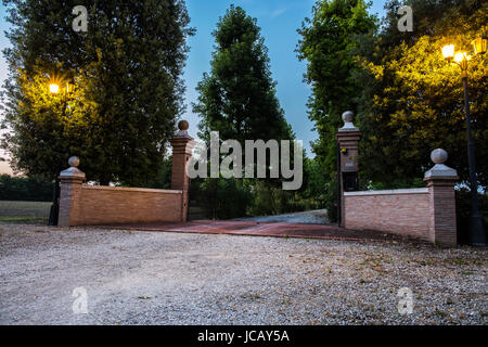 Illuminated entrance to a garden at evening time - Stock Image