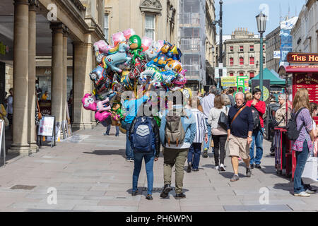 Back view of a seller of helium inflated  bright character balloons in Stall Street the City of Bath - Stock Image