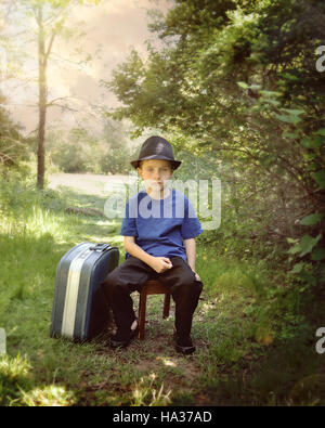 A young boy is sitting on a nature trail in the woods with a suitcase and hat. The child looks sad for a travel - Stock Image