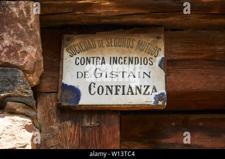 Antique fire insurance porcelain sign of Sociedad de Seguros Mutuos on an old wood door in Gistaín (Chistau valley, Sobrarbe, Huesca, Aragón, Spain) - Stock Image