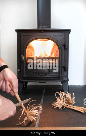 Person Carving Feather Sticks for Kindling to use in a Wood Burning/Multi-Fuel Stove, UK - Stock Image