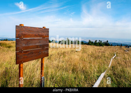 Wooden multi sign on the top of a hill with golden grass in the summer - Stock Image