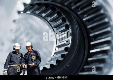 industry workers inside giant gears axles - Stock Image