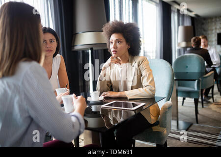 Girls friends in a cafe having a serious conversation over a cup of coffee - Stock Image