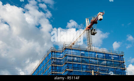 A working tower crane on new home units building site with white cumulus clouds in a blue sky at  Gosford, New South Wales, Australia. - Stock Image