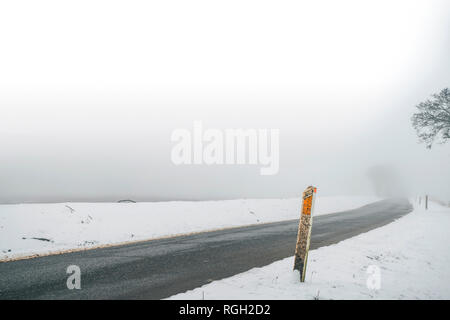 Marker post by a misty road in the winter with snow and a ice highway - Stock Image