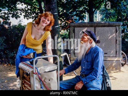 young smiling female tourist with a barrel organ and its operator in hamburg germany during the 1980s - Stock Image