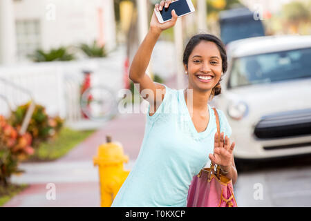 Young woman holding her phone waving her hand for her ride - Stock Image