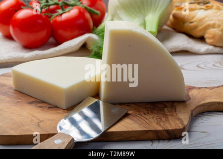 Italian cheese, Provolone dolce cow cheese from Cremona served with olive bread and tomatoes close up - Stock Image