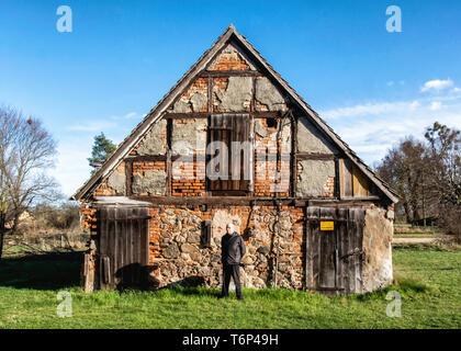 Derelict old barn building with stone exterior and half timbered tudor-style facade on Gutshaus Manor House estate, Friedenfelde,Gerswalde,Brandenburg - Stock Image