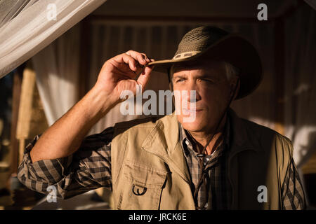 Thoughtful man sitting on canopy bed - Stock Image