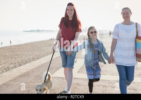 Affectionate lesbian couple with daughter and dog walking on sunny beach boardwalk - Stock Image
