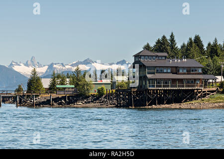 The tiny village of Petersburg on Mitkof Island along the Wrangell Narrows in Frederick Sound with the Alaska Coast Range of mountains behind on Mitkof Island, Alaska. Petersburg settled by Norwegian immigrant Peter Buschmann is known as Little Norway due to the high percentage of people of Scandinavian origin. - Stock Image