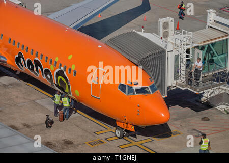 Mango airlines plane at the loading gate. View of nose logo, and maintenance staff working. at airport in Cape Town , South Africa - Stock Image