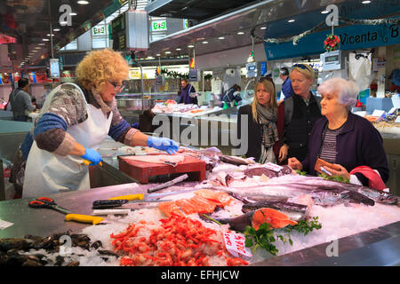 Market trader filleting fish for a customer in the central market of Valencia - Stock Image