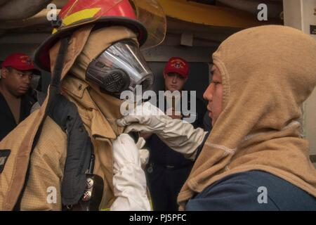 180825-N-HE318-1014 PHILIPPINE SEA (Aug. 25, 2018) Culinary Specialist 2nd Class Allyson Gonzales (right), from San Diego, assists a Sailor dressing out in firefighting gear aboard the Ticonderoga-class guided-missile cruiser USS Antietam (CG 54) during a general quarters training exercise. Antietam is forward deployed to the U.S. 7th Fleet area of operations in support of security and stability in the Indo-Pacific region. (U.S. Navy photo by Mass Communication Specialist 2nd Class William McCann/Released) - Stock Image