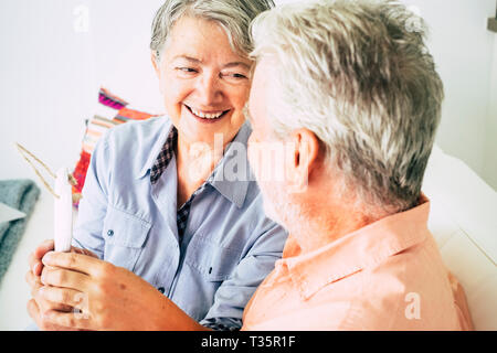 Nice beautiful caucasian senior woman cheerful smiling at  the man sitting with her - relationship and no limit age to flirt or be happy together - lo - Stock Image