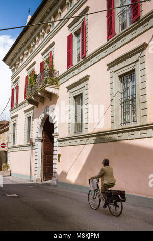 A woman cycling past a grand pink palazzo in the town of Crema, Lombardy, Italy. - Stock Image