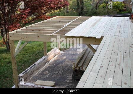 The half finished construction of a wooden outdoor deck in springtime with the framing done and boards nailed down across half of it - Stock Image