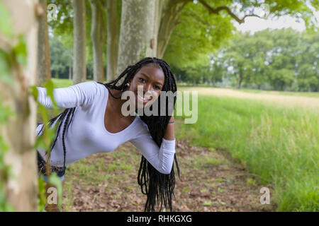 Pretty young African woman with black braids hiding playful behind big trees - Stock Image
